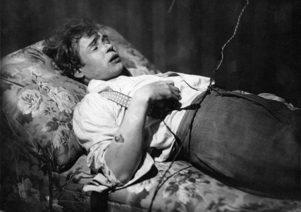 """Снимка на мъртвия поет на диван в хотел """"Англетер"""". На носа му се вижда следа от удар, а на ръката му – рана."""