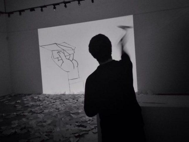 Това, което прави Дечев от 11 до 19 часа всеки ден от живота на изложбата (т.е. през цялото работно време на галерията), e… сгъването на хартиени самолетчета. Снимка: Емил Л. Георгиев - Изражения и случки, поглед от хартиен самолет