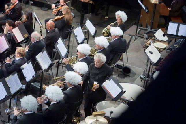 Музикантите от Берлинската филхармония сложиха бели перуки в чест на белокосия диригент Саймън Ратъл. Снимка: Берлинска филхармония - Защо побеляха косите на музикантите в Берлинската филхармония