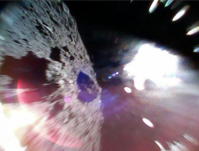 """Снимка, заснета от единия от """"роувърите"""". Бялото петно е от слънчева светлина. Снимка: Хаябуса-2/Туитър - Роботи за пръв път кацнаха на астероид"""